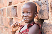 An 11-year-old Ugandan girl smiling, holding a pen against her mouth and leaning against a brick wall looking at the camera