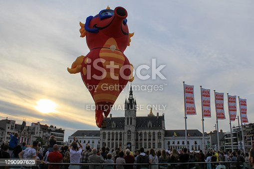 Sint-Niklaas, Belgium - sep 3, 2017: a big red dragon hot air balloon is flying up from the market square in sint-niklaas during sunset in the air with a lot of people watching the spectacle