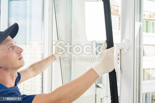 a specialist in installing plastic windows puts a double-glazed window in a window frame, close-up
