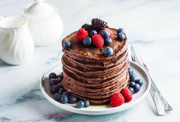 ein stapel schokolade gluten freie pfannkuchen mit frischen beeren. gesundes frühstück am morgen - buchweizenpfannkuchen stock-fotos und bilder