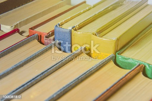 istock a stack of colorful books on the shelf 1005381812