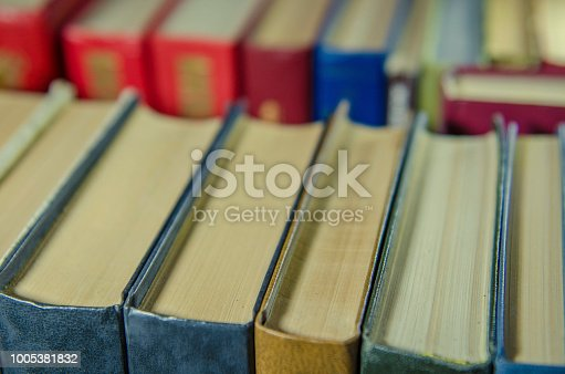 istock a stack of colorful books on the shelf 1005381832