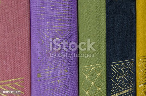 istock a stack of colorful books on the shelf 1005381902