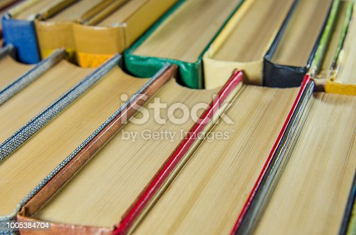 istock a stack of colorful books on the shelf 1005384704