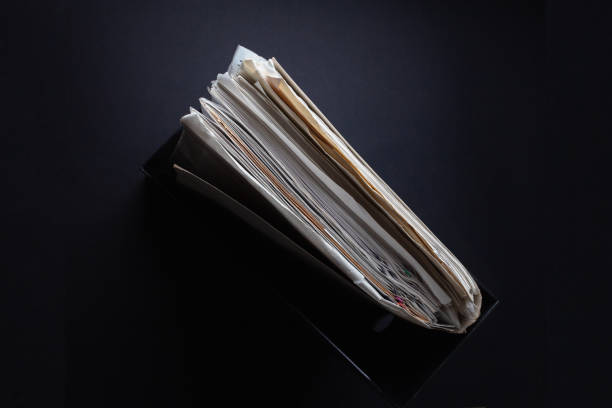 a stack of old papers in a stationery folder on a dark background stock photo
