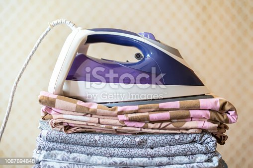 901620964istockphoto a stack of textile bed sheets blankets with iron on top  f 1067694648