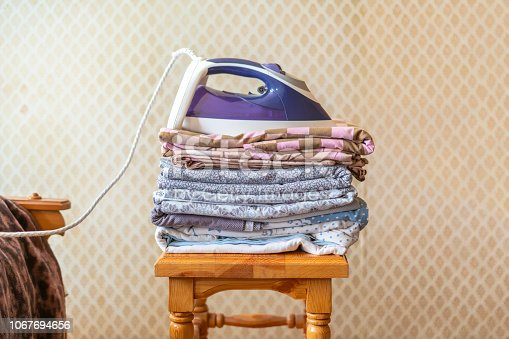 901620964istockphoto a stack of textile bed sheets blankets with iron on top  f 1067694656