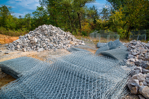 a stone fence in a wire cage