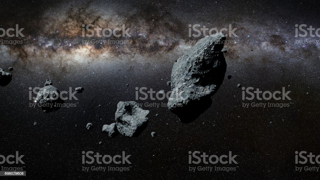 a swarm of asteroids in front of the Milky Way galaxy stock photo