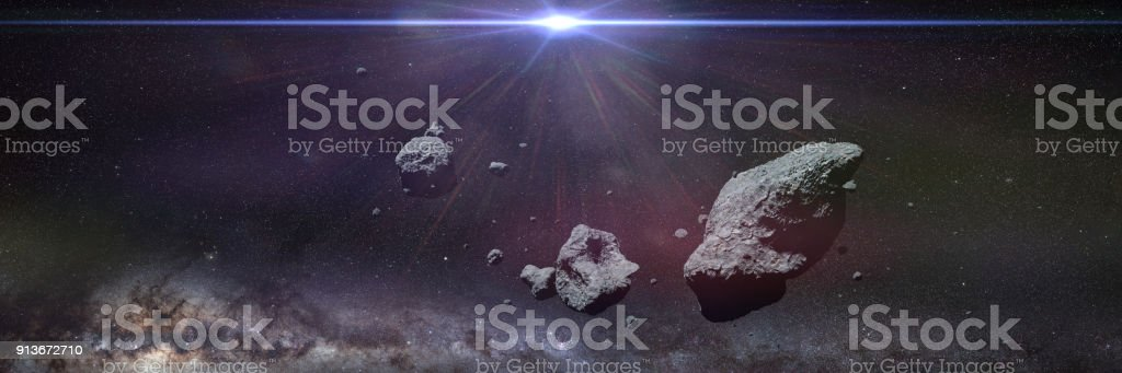 a swarm of asteroids lit by the Sun, space banner stock photo