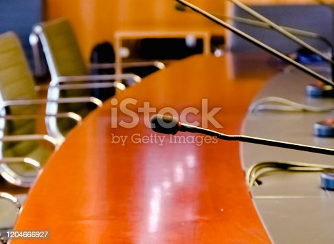 847512708 istock photo a table microphone in a board room with a wooden table and a row of empty chairs 1204666927