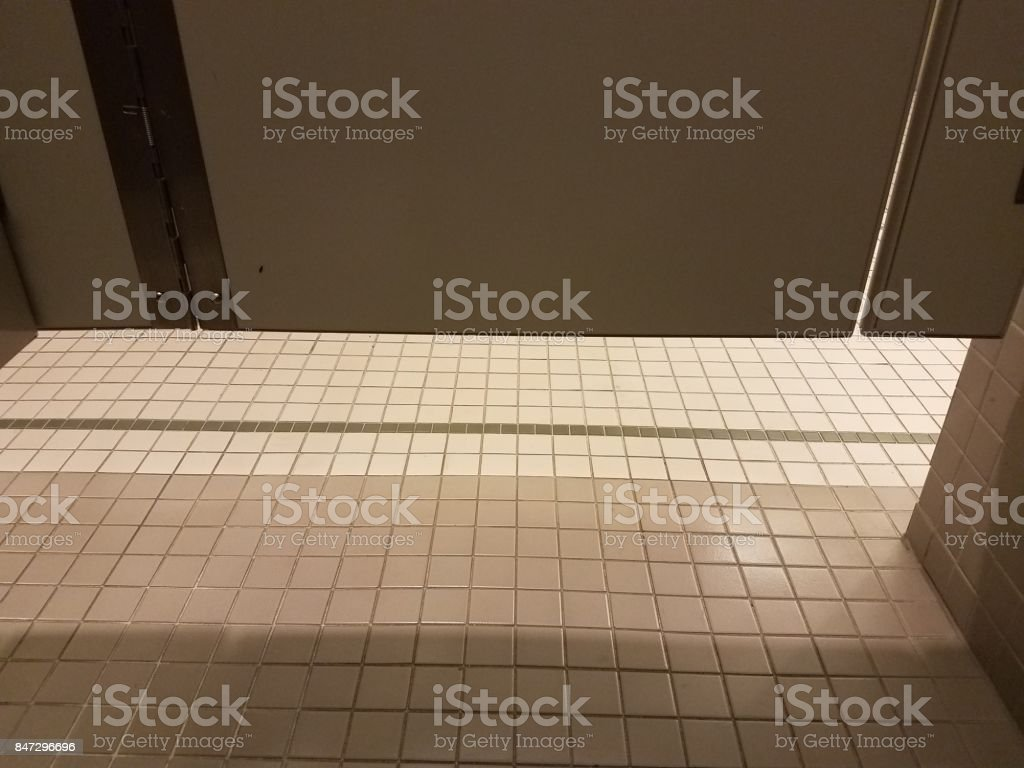 a tiled floor in a bathroom with stall door stock photo