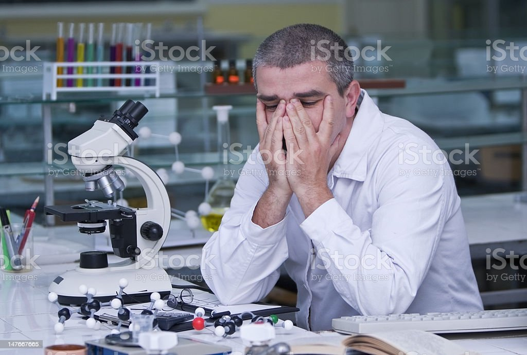 a tired researcher at his workplace royalty-free stock photo