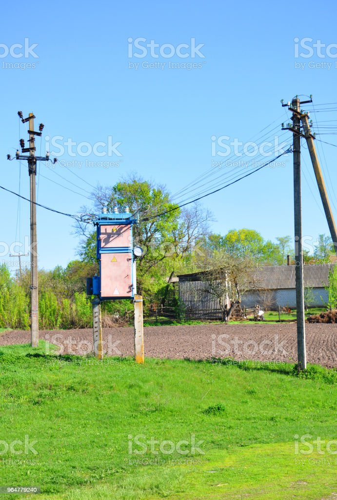 a transformer booth standing on the grass near the pillars royalty-free stock photo