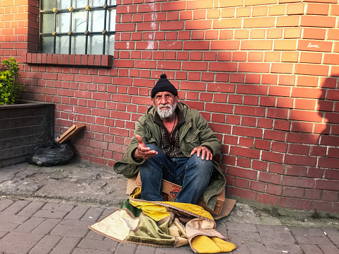 Istanbul, Turkey - April 09, 2018: an old man sitting on the ground and asking for helping panhandler asker aid human relations street city life concepts