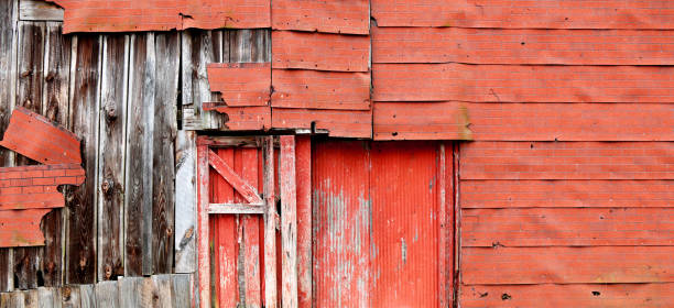 a very old deserted red neglected weathering empty abandoned historic farm barn building structure shed with deteriorating faded siding facade showing a exposed forsaken decay vintage exterior wall stock photo