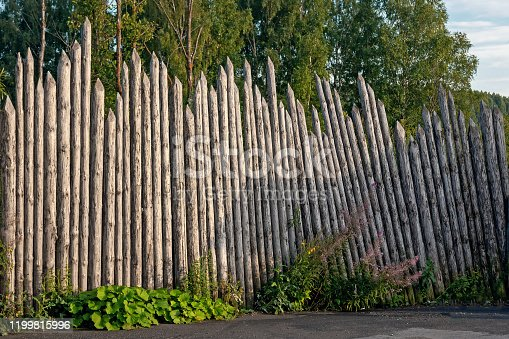 a very old rarity wooden fence made of logs is a good example of ancient architecture
