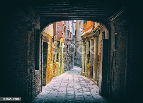 a view of an ancient twisting narrow street of painted old house seen though a dark archway in venice italy