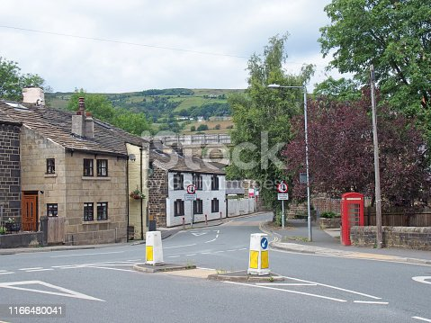 a view of the old village centre of mytholmroyd in west yorkshire with old stone buildings surrounded by pennine countryside