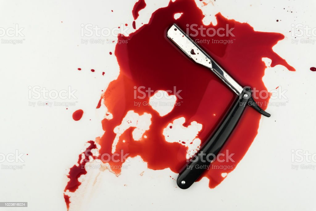 a vintage straight razor in pool of blood stock photo