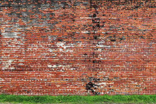 a vintage weathered old manor house old natural red brick garden wall lined with lush green grass perfect for background marketing material as well as wallpaper card poster backdrop stock photo
