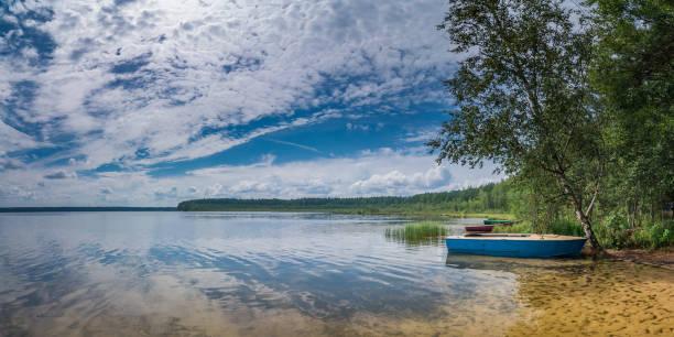 einem warmen Sommertag am Strand. an einem schönen See mit Booten, Bäume und ein Sandboden im seichten Wasser bei bewölktem Himmel blau – Foto
