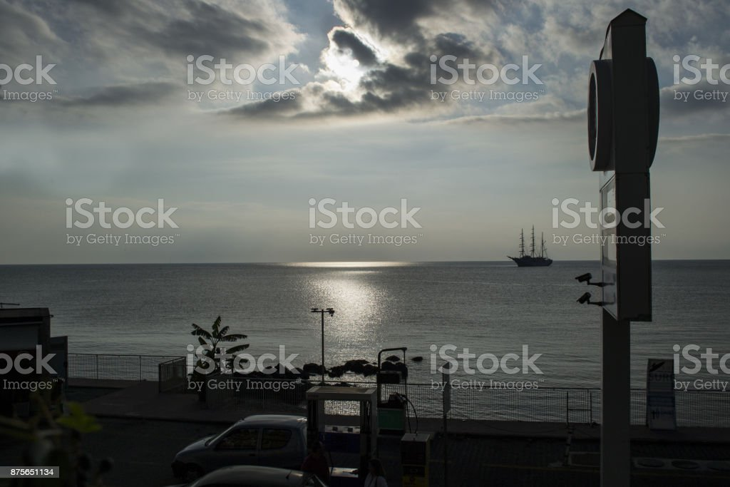 a waterfront with a gas pump and a boat arriving at a port stock photo