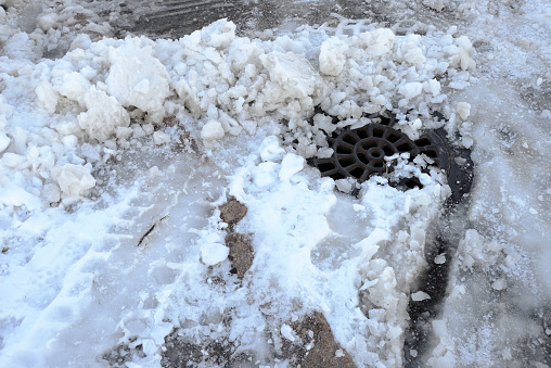 a well of storm sewage covered with snow and ice in winter