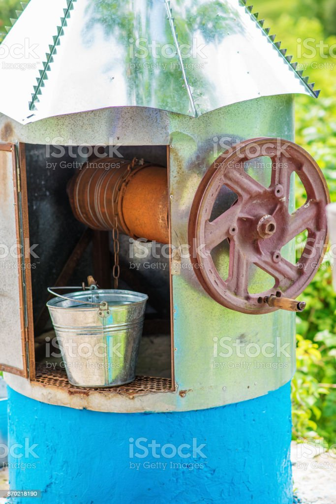 a well with water and a metal bucket near him stock photo