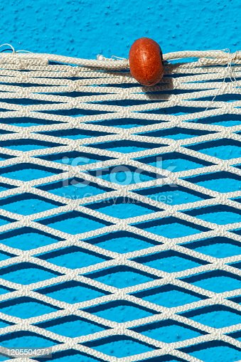 istock a white fisher net hanging on a blue wall 1205504271