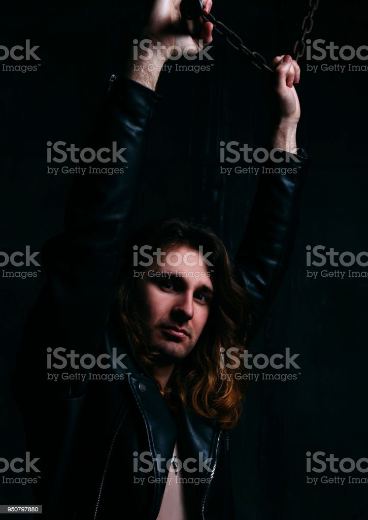 a white man with long hair and a leather jacket clings to the chain and hangs stock photo