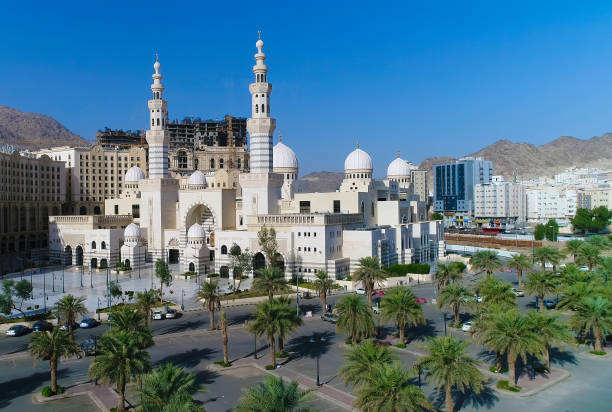 a white mosque in mecca a white mosque in mecca surrounded by buildings and mountains umrah stock pictures, royalty-free photos & images