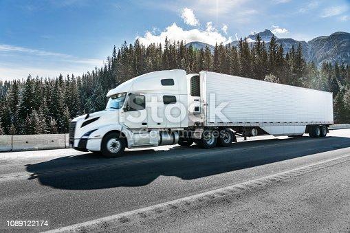 a white semi-truck driving on mountain road,Alberta,Canada.