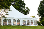 a white wedding tent set up in a lawn surrounded by trees and with the sides down