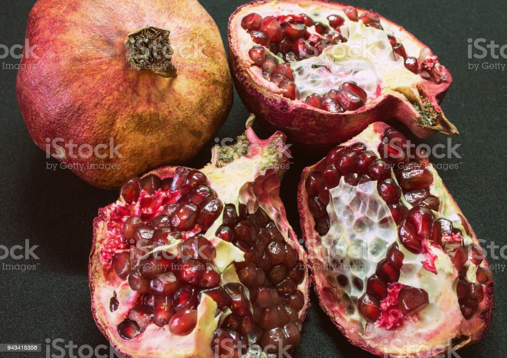 a whole and half-cutted pomegranate on the black background. Pomegranate cut open core. stock photo