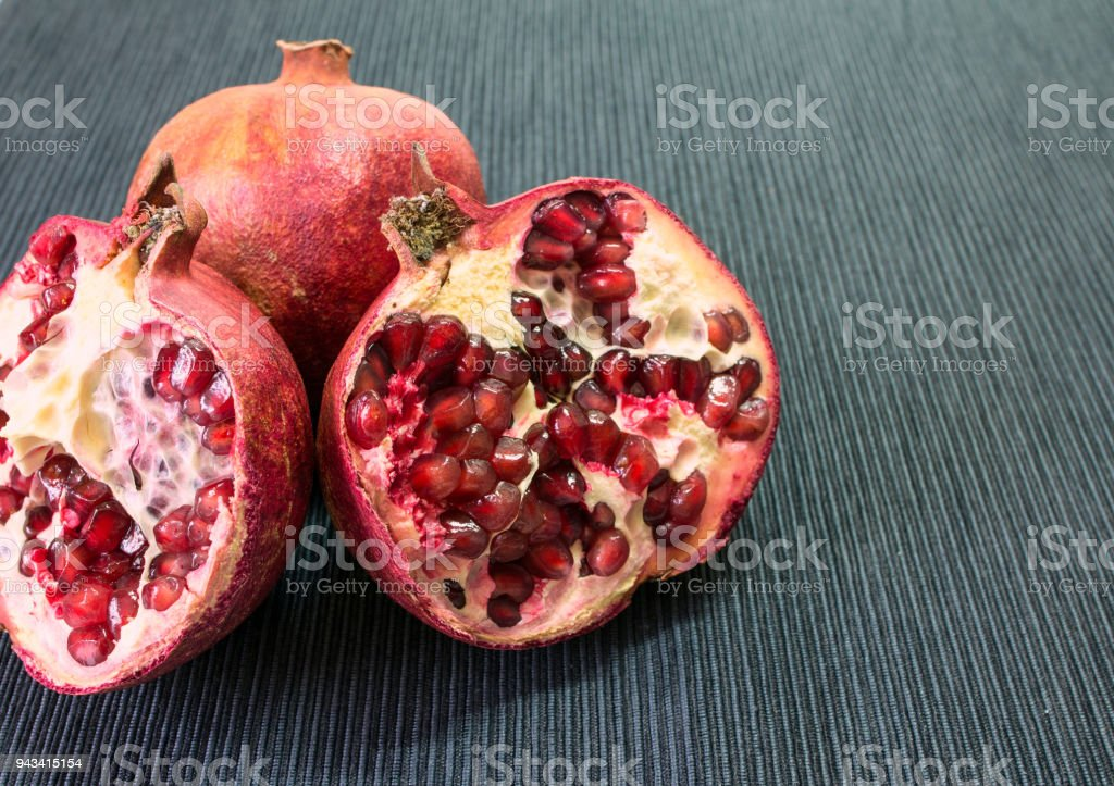 a whole and half-cutted pomegranate on the black background. Seeds of pomegranate. stock photo
