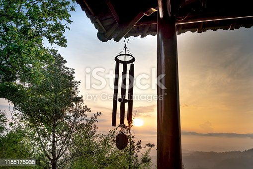 a wind chime hanging from the edge of a temple roof.