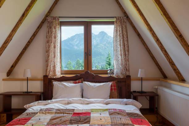 ein fenster in eine handfläche auf der obersten etage eines ländlichen hauses mit einem wunderschönen blick auf die berge - cottage schlafzimmer stock-fotos und bilder