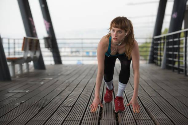 eine sportlerin ist stretching-übungen durchführen. - gedehnte ohren stock-fotos und bilder