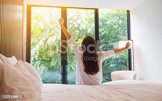 istock a woman do stretching after waking up in the morning  , looking at a beautiful nature view outside bedroom window 1223136812