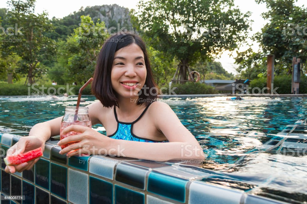 a woman drinking watermelon juice in the pool stock photo