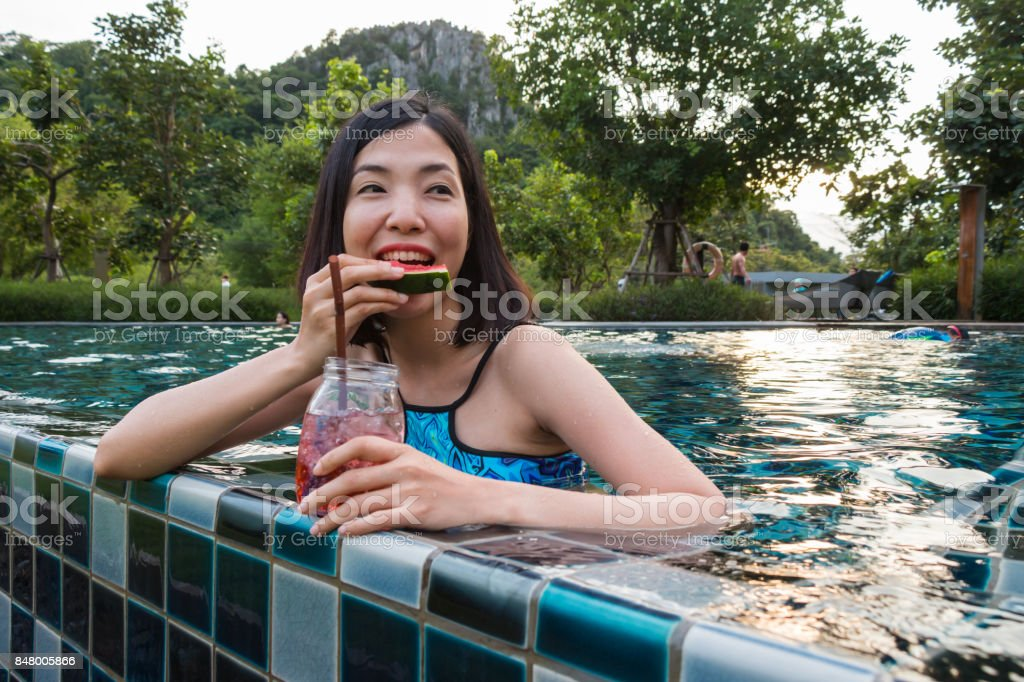 a woman eating watermelon in the pool stock photo