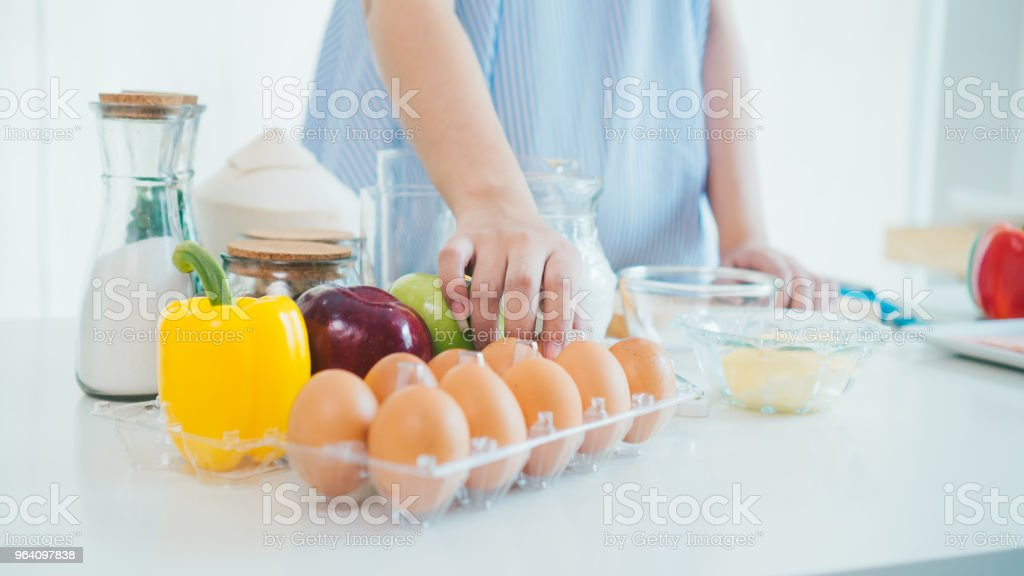 a woman hand in the kitchen in a blue apron takes the egg out of the box. - Royalty-free Abdomen Stock Photo
