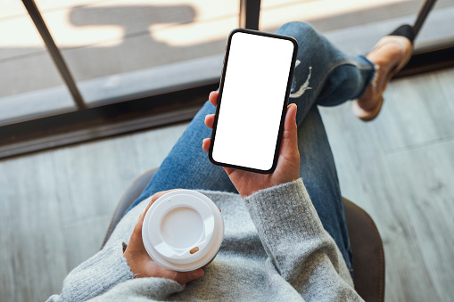 a woman holding a black mobile phone with blank white desktop screen with coffee cup