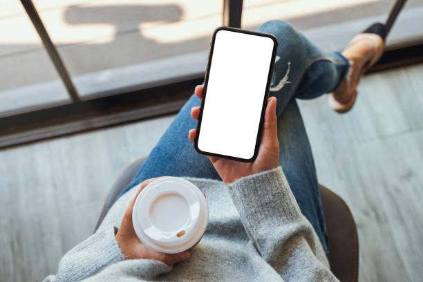 eine Frau hält ein schwarzes Handy mit leerem weißen Desktop-Bildschirm mit Kaffeetasse – Foto