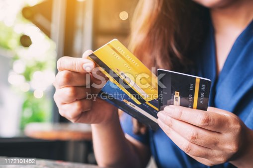 Closeup image of a woman holding and choosing credit card to use