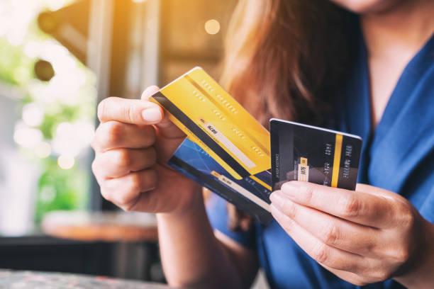 eine frau, die eine kreditkarte hält und wählt, die - konsum stock-fotos und bilder