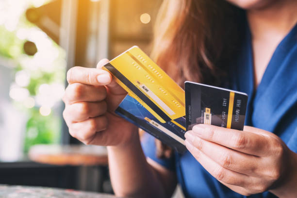 a woman holding and choosing credit card to use Closeup image of a woman holding and choosing credit card to use balance stock pictures, royalty-free photos & images