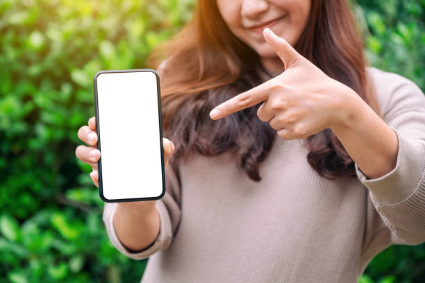 a woman holding and pointing finger at a black mobile phone with blank desktop screen in the outdoors - phone, travelling, copy space imagens e fotografias de stock