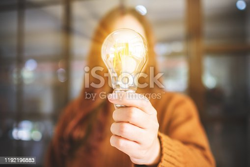 Closeup image of a woman holding and showing a glowing light bulb